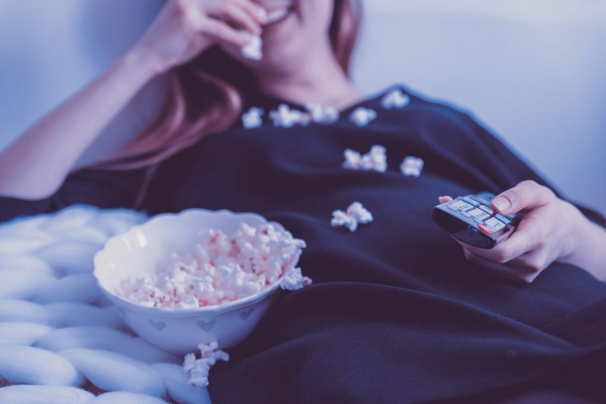Femme mange pop corn et zappe